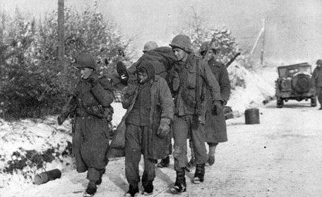 Немецкий военнопленный помогает американским солдатам доставить еще одного раненого немецкого военнопленного недалеко от Харланжа. Декабрь 1944 г.