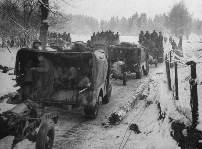 Колонна автомобилей «Додж WC51/52» с полевыми 75-мм гаубицами на дороге в Арденнах. Декабрь 1944 г.