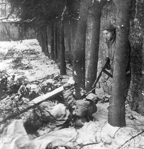 Американский солдат осматривает замерзший труп немца на предмет выявления возможных мин-ловушек возле Вильца. Декабрь 1944 г.