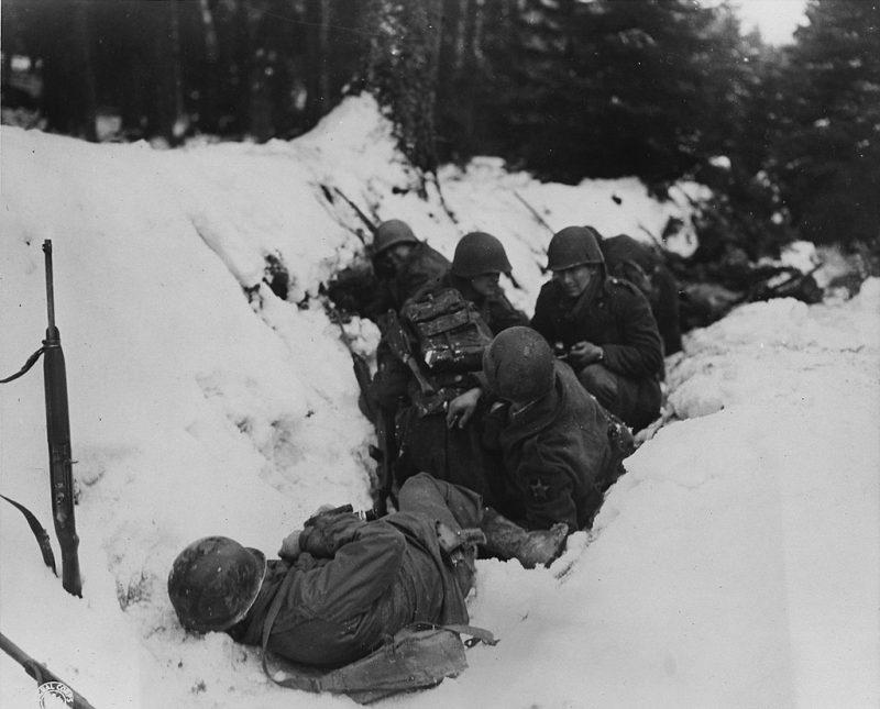Американские пехотинцы 1-й армии США укрываются от немецкого артиллерийского обстрела в лесу Кринкельтер. Декабрь 1944 г.