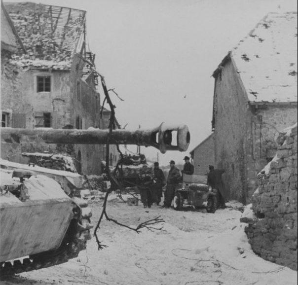 САУ StuG-III и немецкие солдаты на улице бельгийского города во время наступления в Арденнах. Декабрь 1944 г.