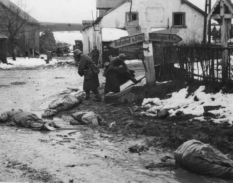 Войска 12-й фольксгренадерской дивизии снимают ботинки и другое снаряжение с тел погибших американских солдат на перекрестке дорог в Хонсфилде, Бельгия, к западу от Лошаймерграбена. Декабрь 1944 г.