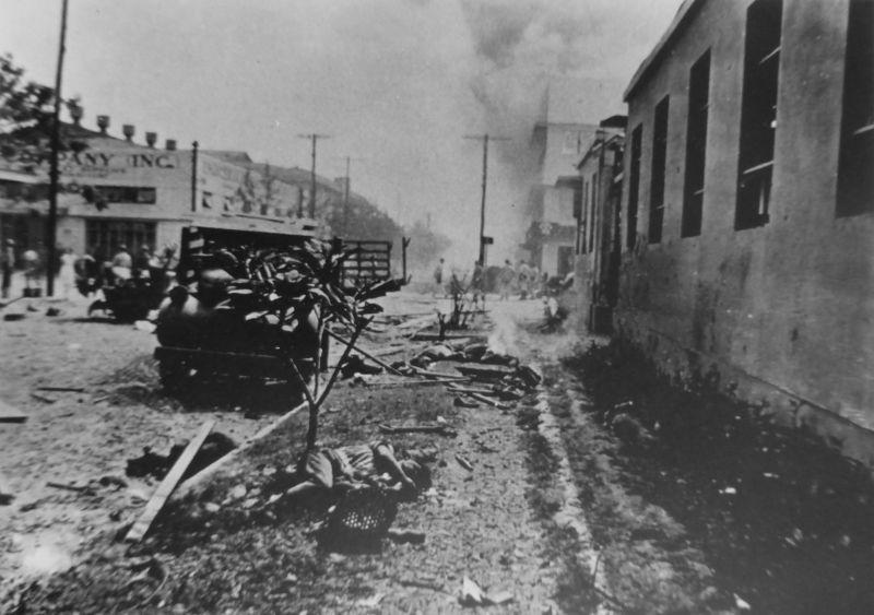 Улица оккупированной японскими войсками Манилы. У дерева перед грузовиком лежит тело погибшего. Январь 1945 г.