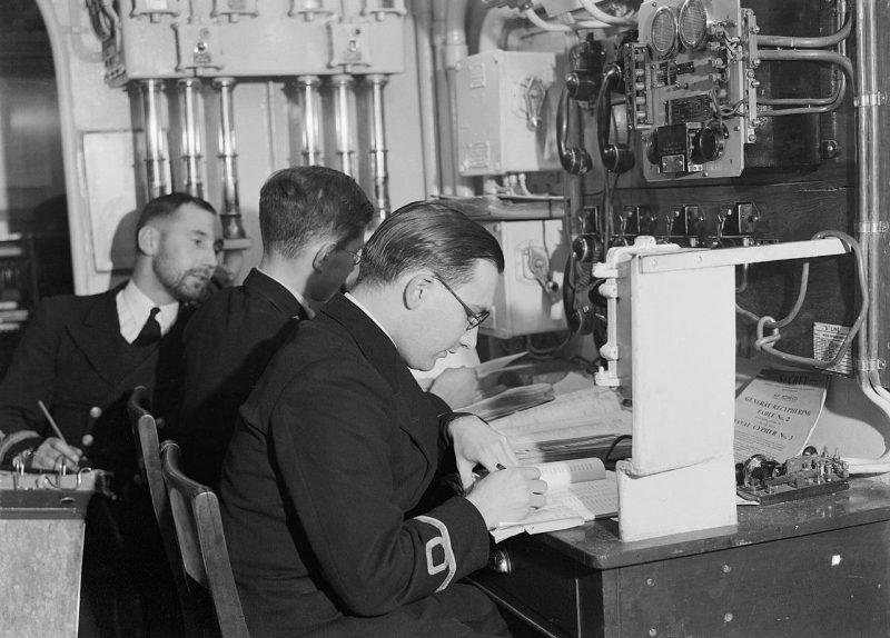 Офицеры HMS «Sheffield» за работой в отделении декодирования во время арктического конвоя в CCCР. Декабрь 1941 г.