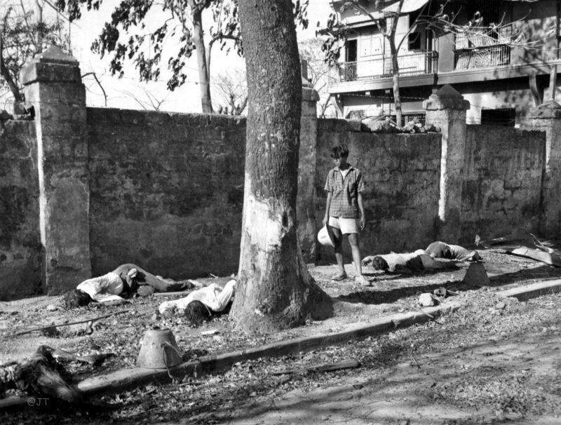 Житель Манилы смотрит на тела убитых японскими солдатами при отступлении из района Эрмита. Февраль 1945 г.