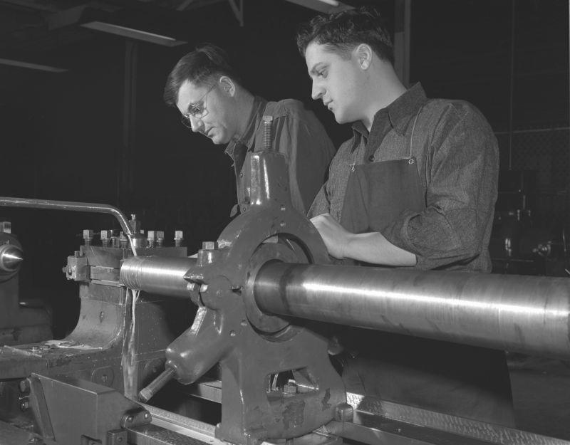 Американские токари обрабатывают ствол 40-мм зенитной пушки «Бофорс» на заводе «Крайслер» в Детройте. 1942 г.