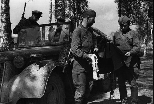 Красноармейцы рассматривают имущество советских граждан, награбленное фашистами в Великих Луках. 15 августа 1941 г.