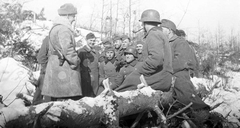 Антифашист - командир Красной Армии Артур Пик беседует с немецкими солдатами, сдавшимися в плен под Москвой и находящимися в сборном лагере в Красногорске. 1941 г.