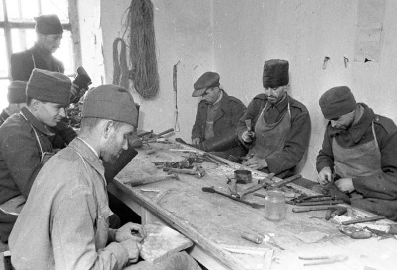 Военнопленные за работой в сапожной мастерской лагеря. 1941 г.