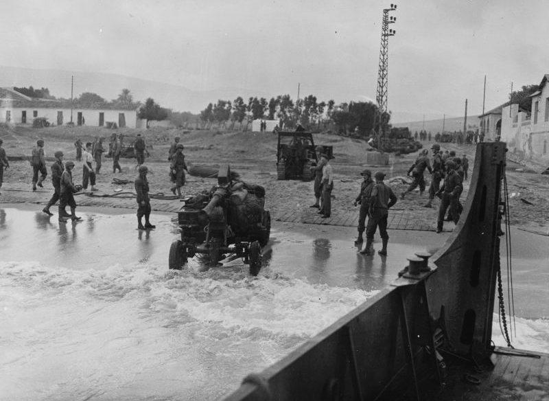 40-мм зенитную пушку «Бофорс», вытаскивает бульдозер на берег с десантного катера. 1943 г.
