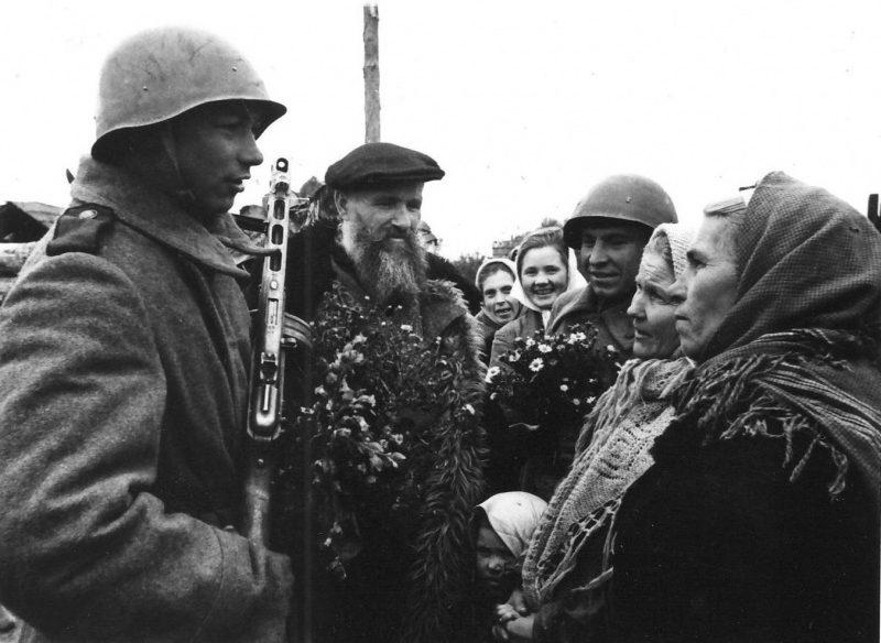 Жители освобожденного Невеля с цветами встречают советских солдат.