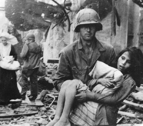 Американский солдат с раненной филиппинкой. Март 1945 г.