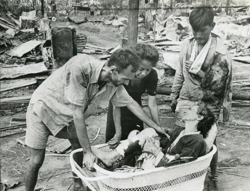 Раненного жителя Манилы соседи в корзине перевозят в госпиталь. Март 1945 г.