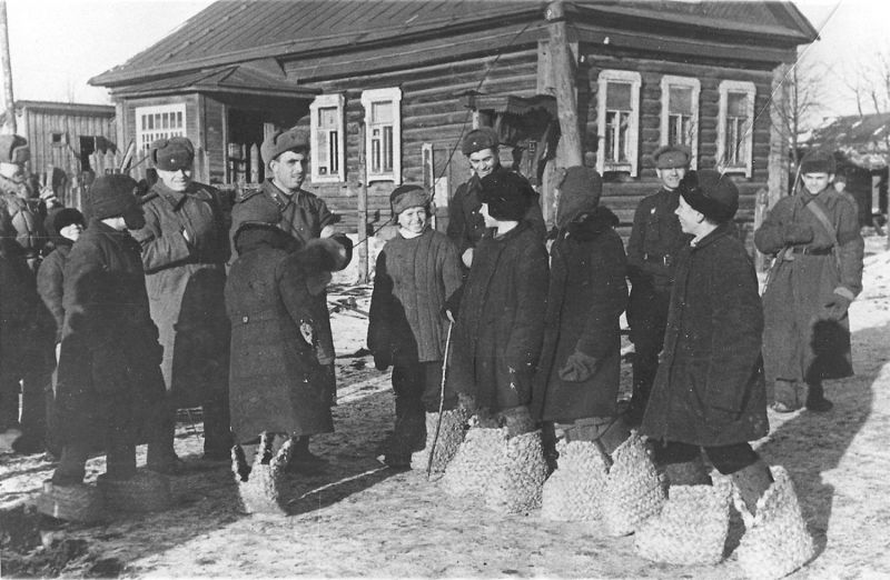 Школьники освобожденного Гжатска показывают красноармейцам немецкие «эрзац-валенки». Март 1943 г.
