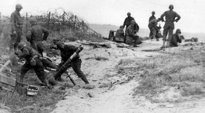 Артиллеристы ведут огонь из 107-мм минометов М2 в месте высадки «Омаха» в Нормандии. Июнь 1944 г.