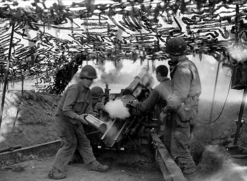 Американские артиллеристы ведут огонь из 105-мм гаубицы в районе Сен-Ло в Нормандии. Август 1944 г.