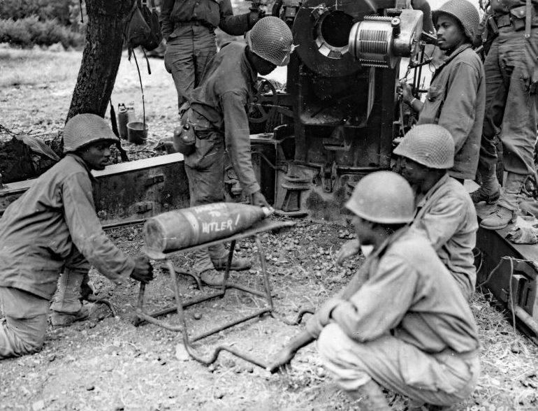Чернокожие американские артиллеристы из расчета 155-мм пушки M1 со снарядом с надписью «Гарлем Гитлеру» во Франции. Август 1944 г.