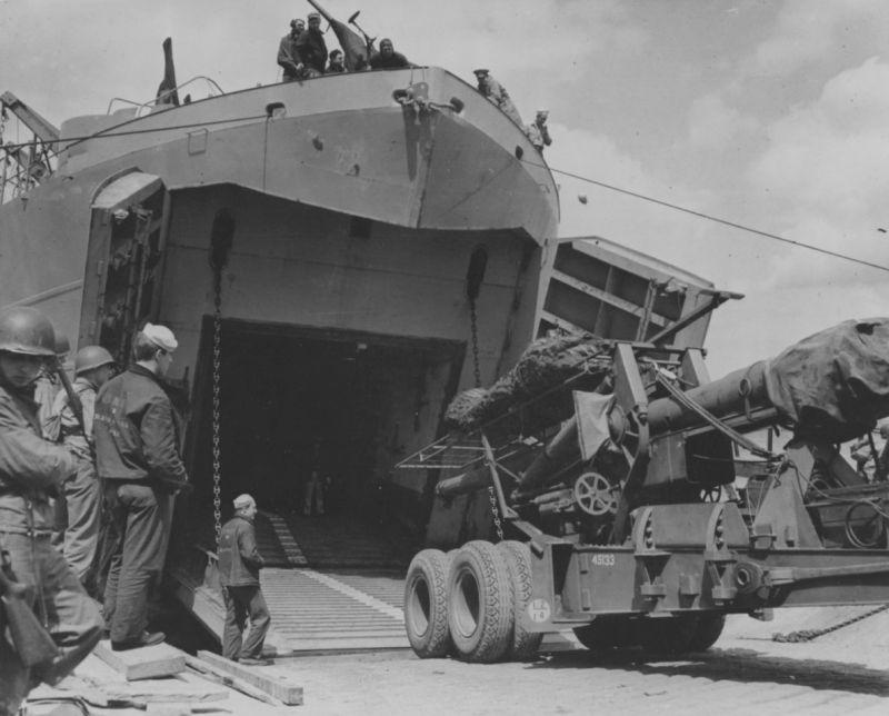 Выгрузка 155-мм полевой пушки М1 на берег в Нормандии с борта десантного корабля. 1944 г.