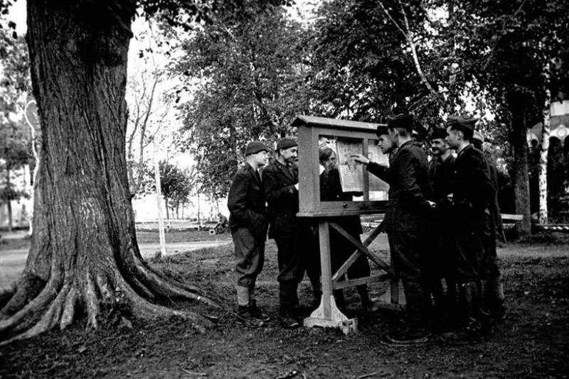 Итальянские и румынские офицеры – военнопленные лагеря № 160 у стенда со свежей газетой. Суздаль, 1943 г.