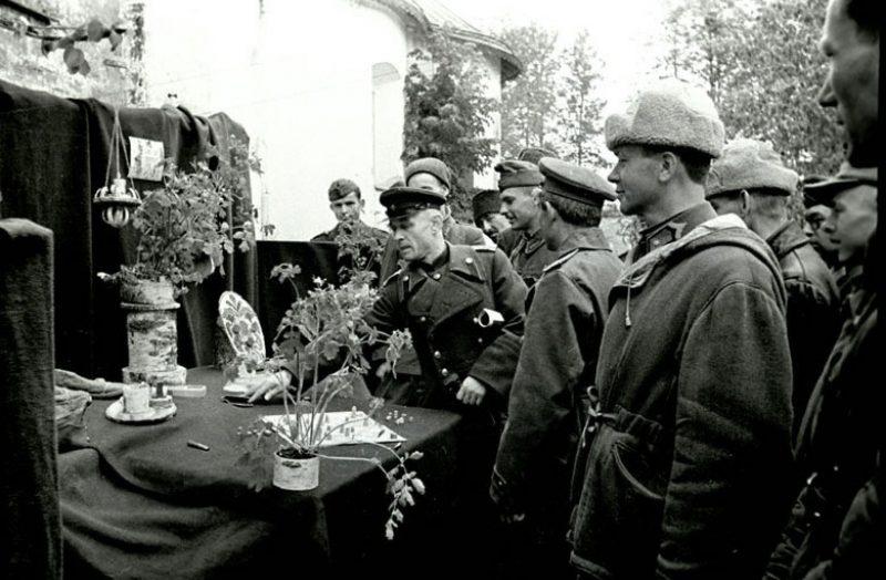 Начальник лагеря военнопленных № 160 полковник А. Новиков и сопровождающие лица осматривают стенд венгров на выставке самодельных вещей, изготовленных военнопленными лагеря. Суздаль, 1943 г.