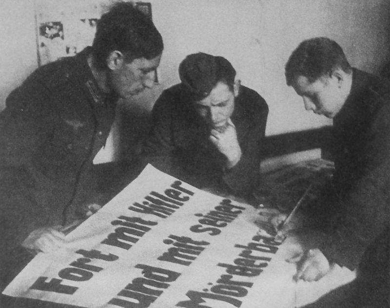 Немецкие военнопленные готовят агитплакат в лагере для пленных. Надпись на плакате - «Fort mit Hitler und mit seiner Mörderba(nde!)» («Долой Гитлера и его банду убийц!»). 1943 г.