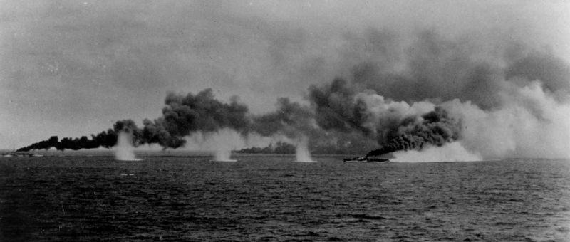 Американский эскортный авианосец USS «Gambier Bay» и корабли эскорта ставят дымовую завесу во время боя у острова Самар. Октябрь 1944 г.