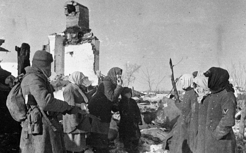 Сельские жители и пленные солдаты Вермахта у разрушенного дома в Украине. 1943 г.