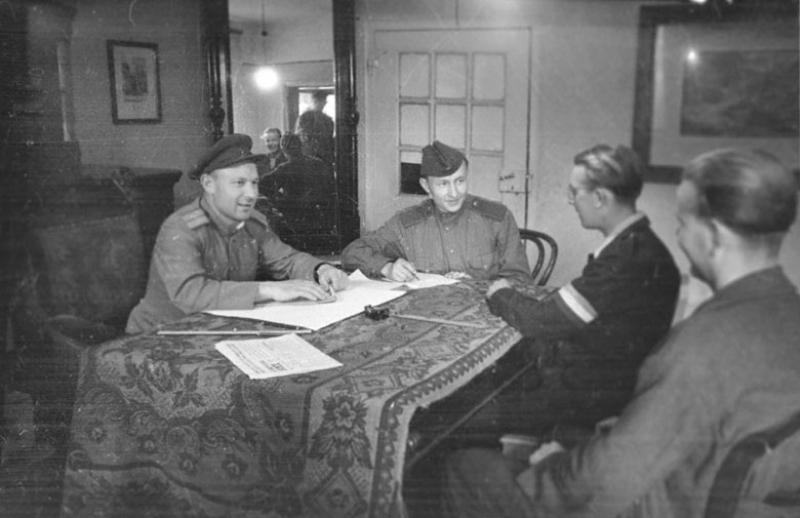 Начальник штаба сборно-пересыльного пункта № 31 репатриации военнопленных капитан И.Л. Горбенко беседует с прибывшими иностранными военнопленными. 1945 г.