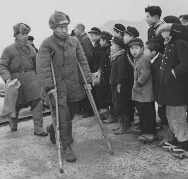 Двое вернувшихся из СССР японских пленных проходят мимо группы встречающих. 1946 г.