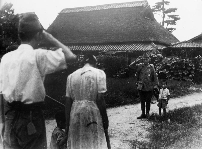 Вернувшийся домой бывший японский военнопленный приветствует семью земляков. 1946 г.
