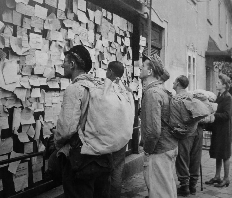 Бывшие военнопленные, вернувшиеся в Германию из СССР, читают объявления о розыске родственников, оказавшихся в плену, в приемном «лагере Фридланд». 1955 г.