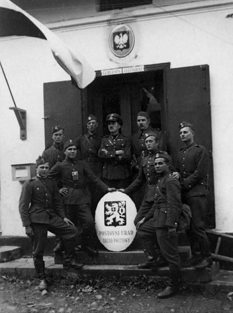 Польские солдаты позируют с низложенным чехословацким гербом у захваченного ими в ходе операции «Залужье» здания телефона и телеграфа в чешском селении Лиготка Камеральна, расположенного недалеко от города Тешин. Октябрь 1938 года.
