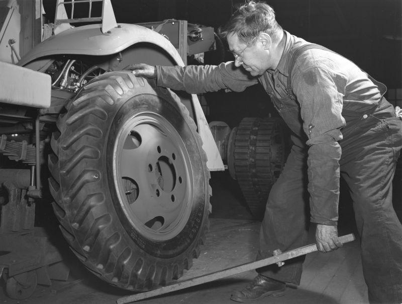 Рабочий американского завода «Уайт мотор компани» устанавливает колесо на бронетранспортер М2. Декабрь 1941 г.