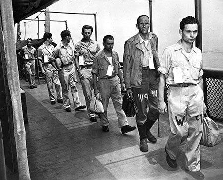 Прибытие военнопленных в лагерь. Нашивка «PW» на их униформе обозначает статус военнопленных.