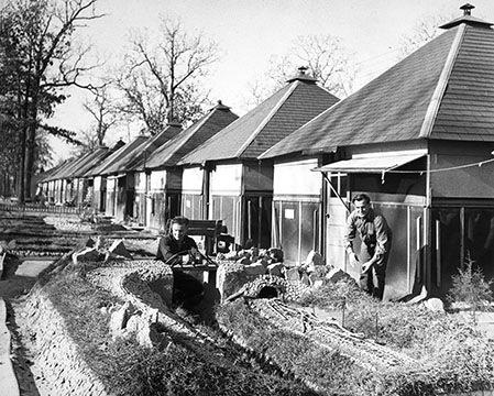 Немецкий генерал и его денщик из военнопленных ухаживают за садом в лагере Боуи у своего бунгало. 1944 г.