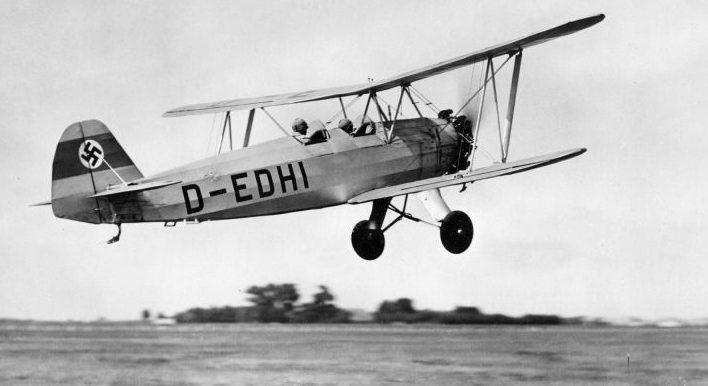 Учебно-тренировочный самолет-биплан Фокке-Вульф Fw.44 взлетает с аэродрома авиашколы. 1940 г.