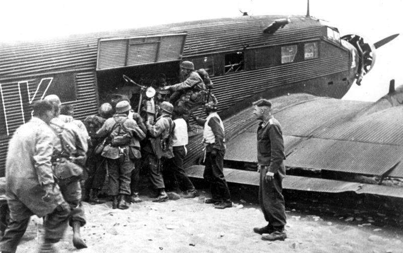 Немецкие парашютисты выгружают мотоцикл из транспортного самолета Ю-52 на Крите. Май 1941 г.