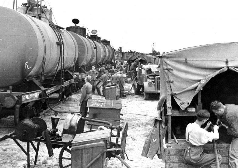 Немецкие грузовики заправляются топливом на железнодорожной станции в СССР. Июль 1941 г.