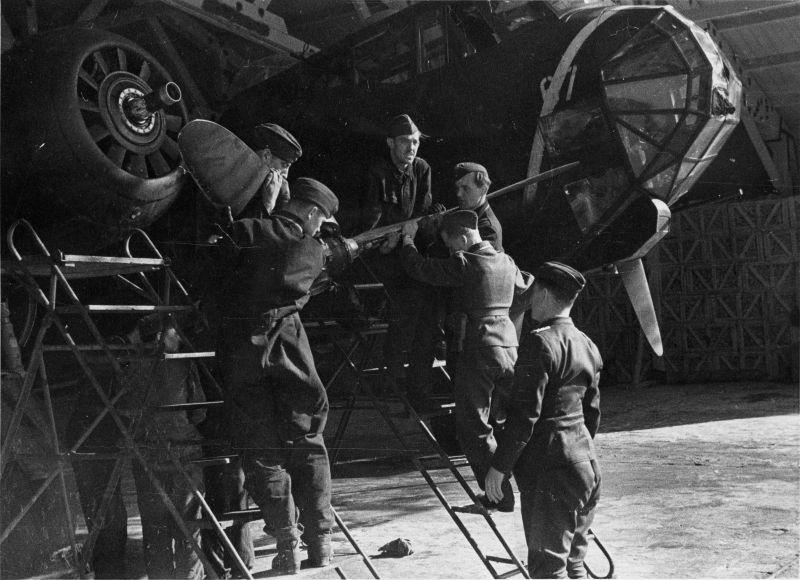 Авиатехники устанавливают воздушный винт на бомбардировщик Дорнье Do-217 в ангаре аэродрома Схипхол под Амстердамом. Май 1942 г.