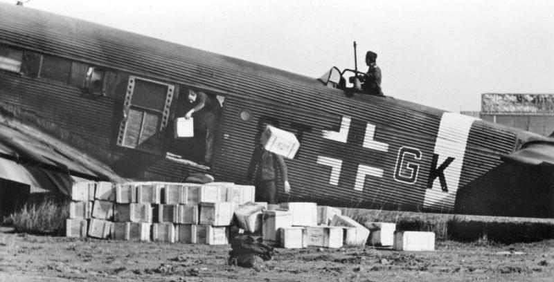 Разгрузка припасов из транспортного самолета Junkers Ju.52/3m в Тунисе. Январь 1943 г.