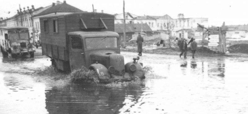 Грузовик «Phänomen Granit 30» и автобус «MAN Е3000» на улице оккупированного советского города. 1942 г.