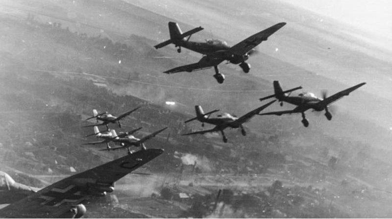 Пикирующие бомбардировщики Ю-87 в полете над советским населенным пунктом.1943 г.