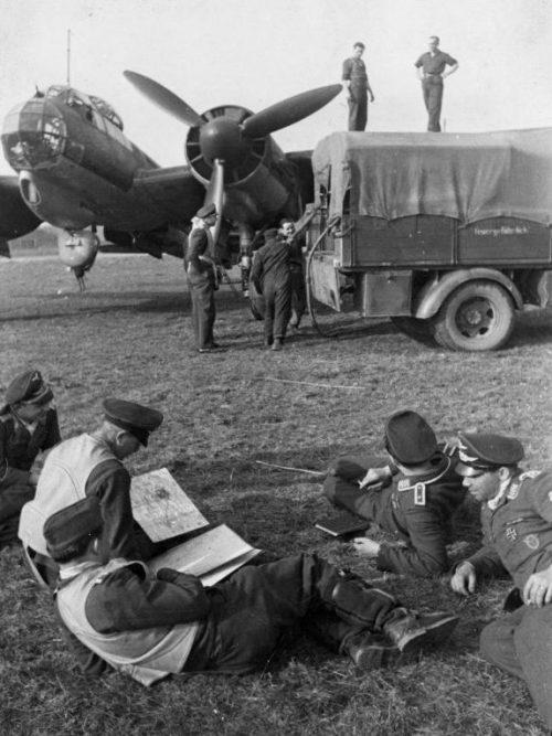 Экипаж бомбардировщика Ю-88 ждет завершения заправки самолета перед вылетом на аэродроме во Франции. Апрель 1944 г.