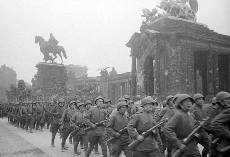 Советские колонны идут мимо Рейхстага.