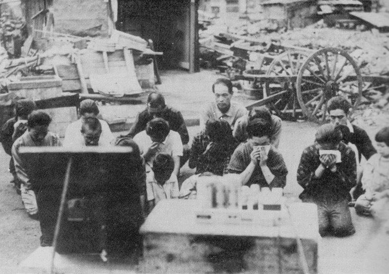 Мирные жители Японии слушают передачу Императора, читающего Императорский рескрипт капитуляции.