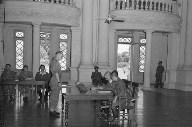 Командующий японскими войсками в Бирме Итида Дзиро подписывает капитуляцию перед британскими войсками бригадного генерала Армстронга в рангунском Доме правительства.