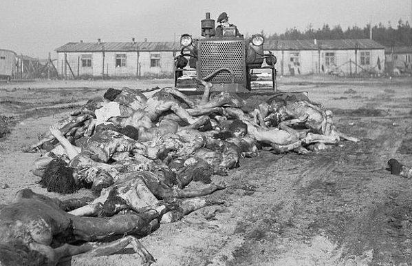 Британский бульдозер «толкает» узников к братской могиле.