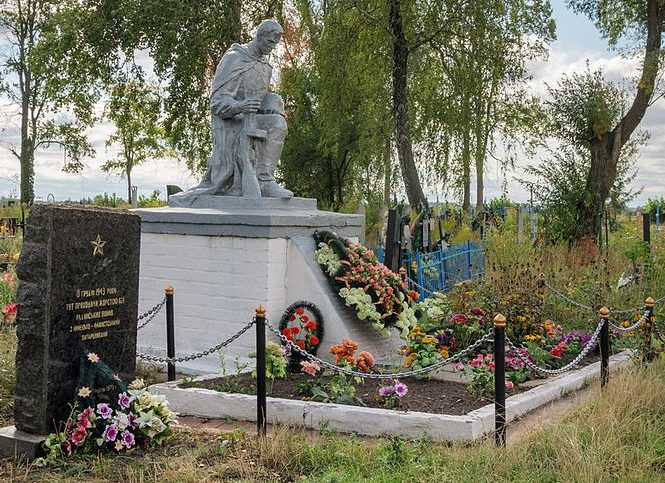 с. Дворец Житомирского р-на. Памятник, установленный на братской могиле, в которой похоронено 33 советских воинов и памятный знак на месте боев.