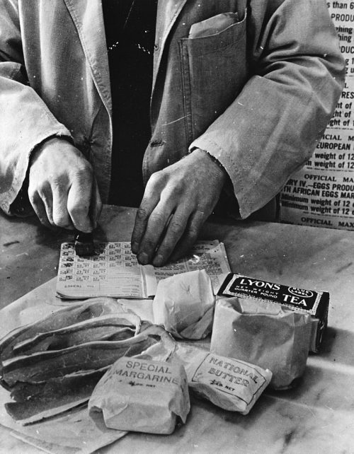 Продавец магазина отмечает купоны в карточке британской домохозяйки в 1943 году.