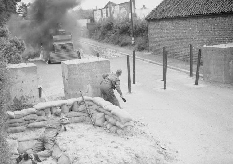 Ополченцев атакует вражеский «танк» во время защиты бетонного дорожного заграждения с помощью бомб с зажигательной смесью. Август 1940 г.